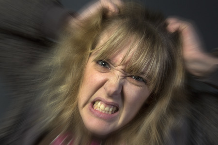 A very angry young woman tearing her hair out  Stock Photo