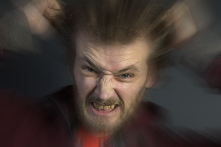 frantic: An angry man with a bad temper tearing his hair out