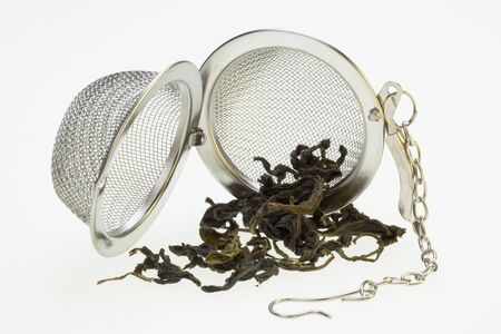 infusing: A Tea Infusing Basket or Brewing Basket and green tea. Stock Photo