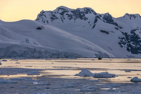 antarctic: Tourist icebreaker in the dramatic scenery of the Lemaire Channel on the Antarctic Peninsula in Antarctica. Photo taken at 3am by the light of the Midnight Sun. Stock Photo