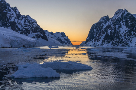 antarctic peninsula: Tourist icebreaker in the dramatic scenery of the Lemaire Channel on the Antarctic Peninsula in Antarctica. Photo taken at 3am by the light of the Midnight Sun. Stock Photo