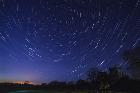 cosmology: Astronomy - Star Trails in early Spring above a church in a small village in North Yorkshire in the United Kingdom.