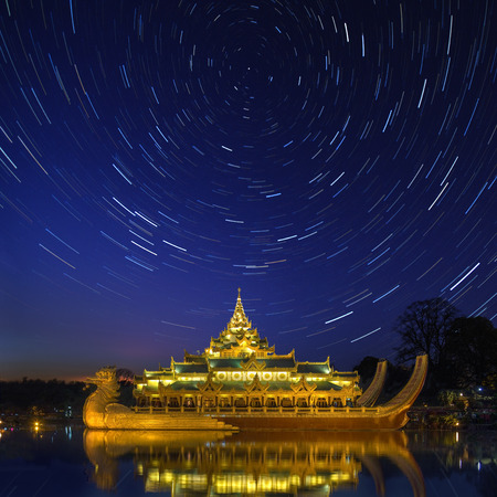 cosmology: Star trails above the Karaweik, a replica of a Burmese Royal Barge on Kandawgyi Lake in Yangon in Myanmar. Although a national landmark it now houses a restaurant.