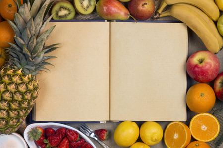 recipe book: A selection of fresh fruit and a recipe book - Space for text