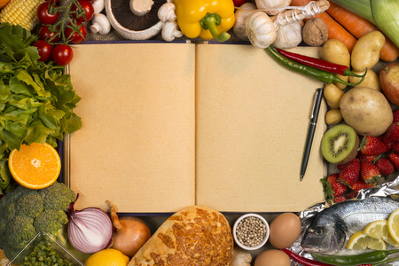 recipe book: Staple foods - Fruit, Fish, Bread and Vegetables with the blank pages of a recipe book - Space for text.