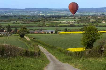 north yorkshire: Hot air balloon drifting over the Harwardian Hills in North Yorkshire in the northeast of England.