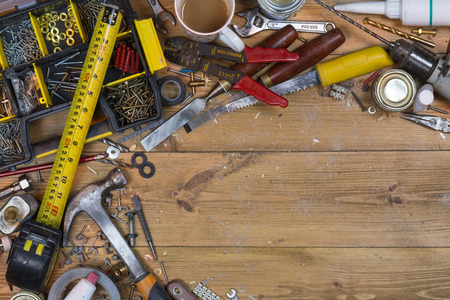 untidy text: Home maintenance - An untidy workbench full of dusty old tools and screws with space for text.