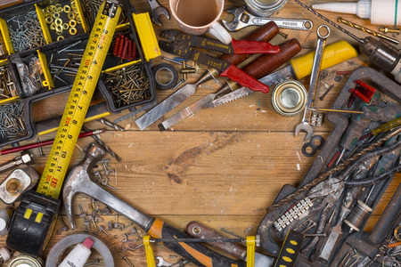 Home maintenance - An untidy workbench full of dusty old tools and screws with space for text.