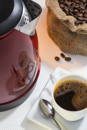 electric kettle: A cup of fresh coffee and reflection on the side of an electric kettle