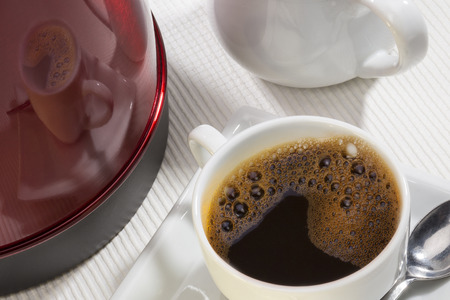 electric kettle: A cup of hot black coffee and reflection on the side of an electric kettle