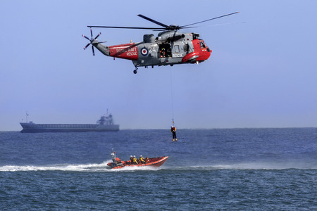 A Royal Navy Sea King Search and Rescue helicopter lifting a casualty from a small boat in a busy shipping lane off the northeast coast of the United Kingdom.