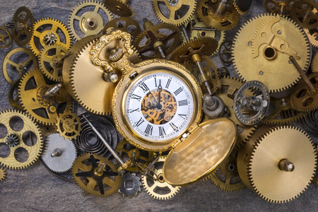 disassemble: Pocket watch and a selection of dusty old brass clock parts.