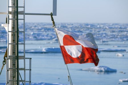 polar environment: Flags of Greenland flying from the mast of a tourist icebreaker