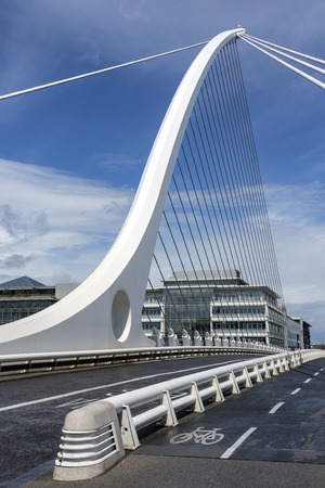 samuel: The Samuel Beckett Bridge and the building on the waterfront near the Convention Center - Dublin city center in the republic of Ireland. This is a cable-stayed bridge that joins Sir John Rogersons Quay on the south side of the River Liffey to Guild Stree Editorial