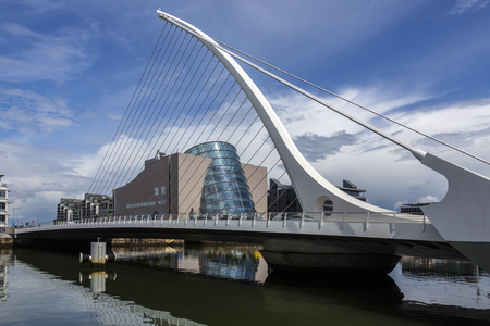 The Samuel Beckett Bridge and the building on the waterfront near the Convention Center - Dublin city center in the republic of Ireland. This is a cable-stayed bridge that joins Sir John Rogersons Quay on the south side of the River Liffey to Guild Stree Editorial