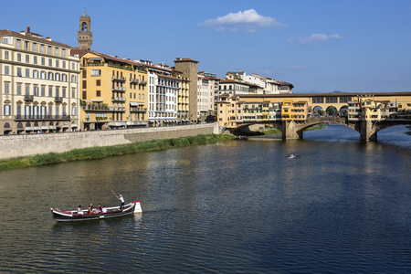 Florence, Italy - The Ponte Vecchio (Old Bridge] is a Medieval stone bridge over the Arno River. Noted for still having shops built along it, as was once common. Butchers initially occupied the shops; the present tenants are jewelers, art dealers and souv