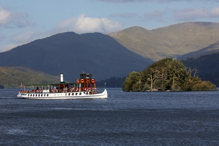 Tourist boat near Bowness on Lake Windermere in the Lake District in Cumbria in the northwest of England in the United Kingdom. Windermere is the largest natural lake in England and is within the Lake District National Park. Stock Photo
