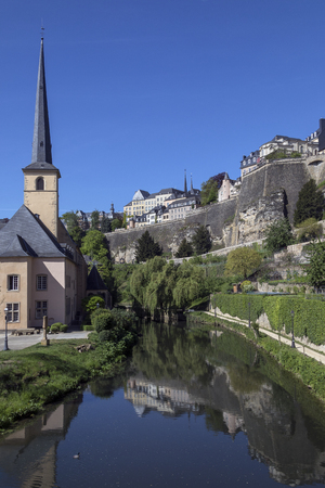 spire: Luxembourg City - Ville de Luxembourg. St John Neimenster and the walls of the old town viewed from the Grund area of the city.