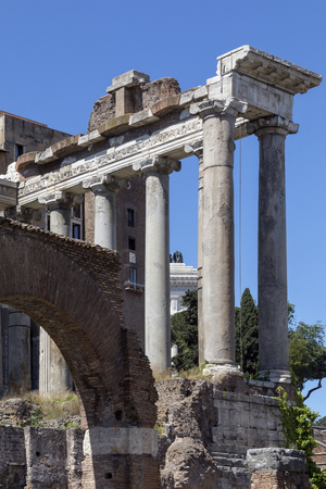 The Temple of Saturn in the Roman Forum in the city of Rome, Italy. Gradual collapse over the centuries has left nothing but the front portico standing. The ruins of the temple stand at the foot of the Capitoline Hill in the western end of the Forum Roman Stock Photo