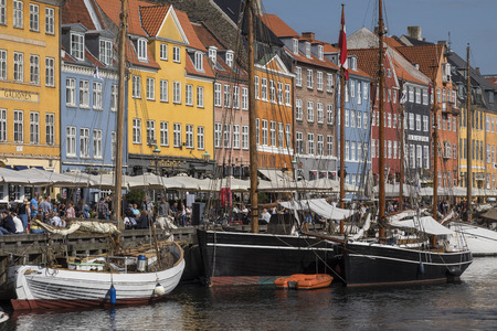 townhouses: Copenhagen - Denmark.  Nyhavn or New Harbour  is a 17th century waterfront, canal and entertainment district from Kongens Nytorv to the harbour front. It is lined by brightly coloured 17th and early 18th century townhouses, bars, cafes and restaurants. It Editorial
