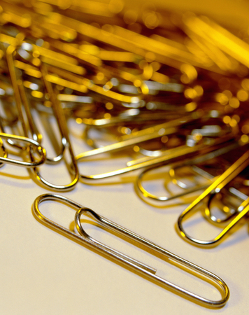 A pile of paper clips - used in the office to clip papers and documents together in a temporary non-damaging way (unlike staples).