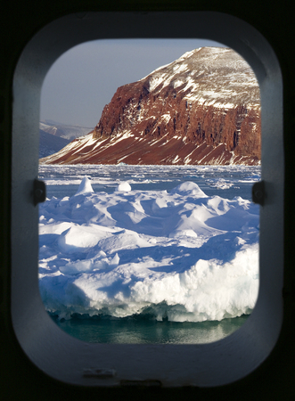 Davy Sound in King Oscars Fjord on the east coast of Greenland. Viewed through a ships porthole.