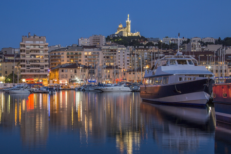The Vieux Port area of Marseille in the Cote dAzur region of the South of France. Looking towards the Cathedral de Notre-Dame-de-la-Garde high on a hill overlooking the city.