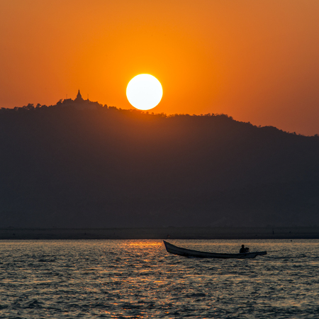 Sunset on the Irrawaddy River in Myanmar (Burma).  It is the countrys largest river and most important commercial waterway. Originating from the confluence of the Nmai and Mali rivers, it flows relatively straight North-South before emptying through the Irrawaddy Delta into the Andaman Sea.