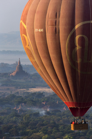 Tourists in a hot air balloon flying over the temples of the Archaeological Zone in Bagan in the early morning sunlight.  Myanmar (Burma).