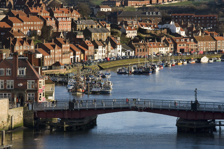 Late afternoon sunlight on the harbor bridge and harbor front buildings of Whitby on the North Yorkshire coast in northern England.