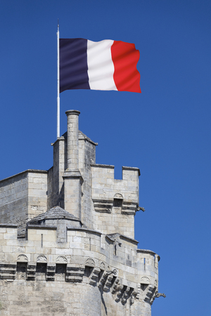 The French national flag flying from the tower of  La Tour de la Lanterne in the port of La Rochelle in the Charente-Maritime region of France.