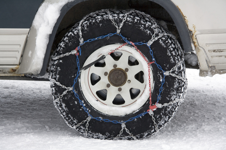 Snow chains on the wheel of a 4X4 vehicle in Greenland. Standard-Bild - 117078604