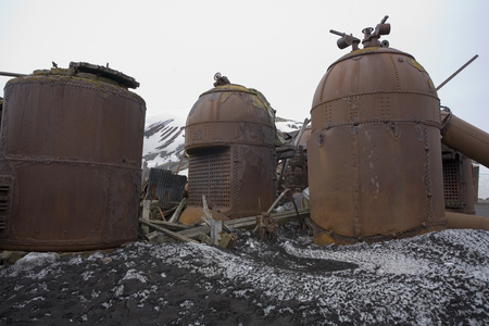 Rusting remains of the boilers of an old abandoned whaling station on Deception Island in Antarctica.
