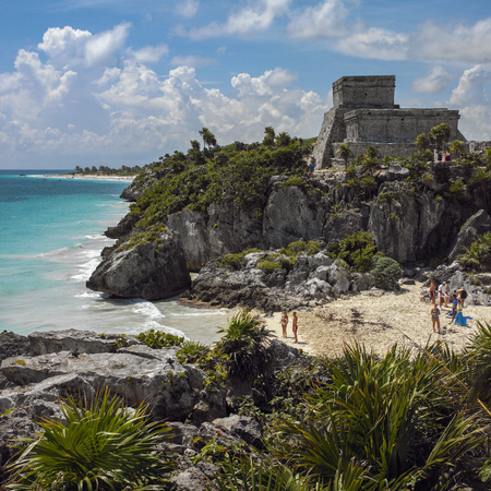 Tourists on a beach by the ancient pre-Columbian ruins of a Mayan temple at Tulum near Cancun on the Yucatan Peninsula in Mexico. 新聞圖片