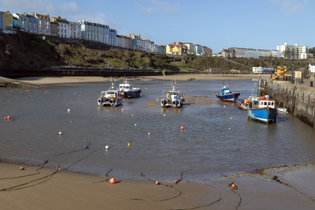 Tenby harbor in Carmarthen Bay at low tide - Tenby in Pembrokeshire, south Wales in the United Kingdom. Stock Photo