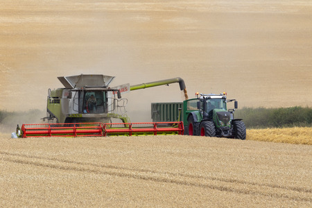 A combine harvester working in a field of wheat in North Yorkshire in the United Kingdom.