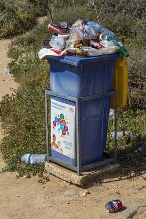 Overflowing rubbish bin - on a beach in the Algarve in southern Portugal. Editöryel