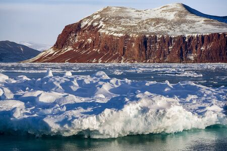 Sea ice and dramatic landscape of Davy Sound in King Oscars Fjord on the east coast of Greenland.