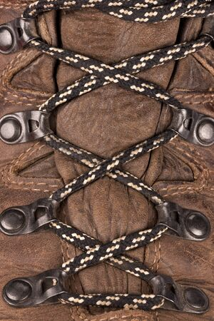 Laced up boots - laces are a cord or leather strip passed through eyelets or hooks on opposite sides of a shoe or garment and then pulled tight and fastened.