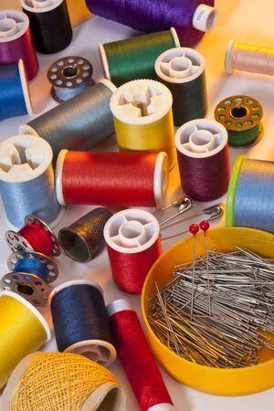 Colorful selection of cotton spools and pins used for sewing.