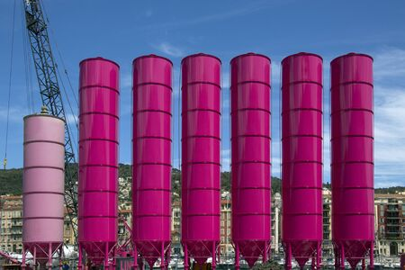 A row of cement hoppers on a construction site in the harbor at Nice in the South of France. Stockfoto