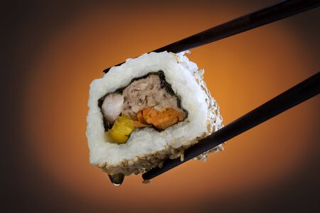 Sushi is a Japanese dish consisting of small balls or rolls of vinegar-flavoured cold rice served with a garnish of vegetables, egg, or raw seafood.