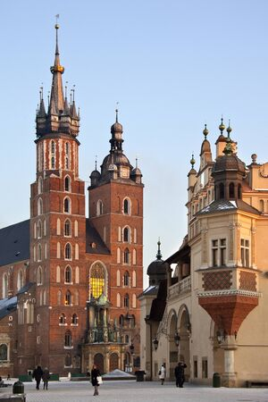 The 13th Century Church of St Mary and the north end of the Cloth Hall in the Main Square (Rynek Glowny) in the city of Krakow in Poland. The Gothic basilica is also known as the Church of the Assumption of the Virgin.