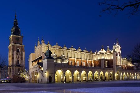 Nightime view of the Town Hall Tower and the south west end of the Cloth Hall (Sukiennice) in the main market square in Krakow in Poland.