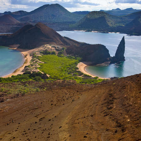 Pinnacle Rock and a volcanic landscape of cinder cones and lava fields on the island of Bartolome in the Galapagos Islands, Ecuador. Stok Fotoğraf