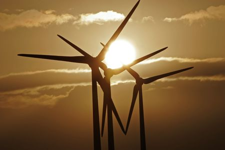 Wind turbines silhouetted against a sunset