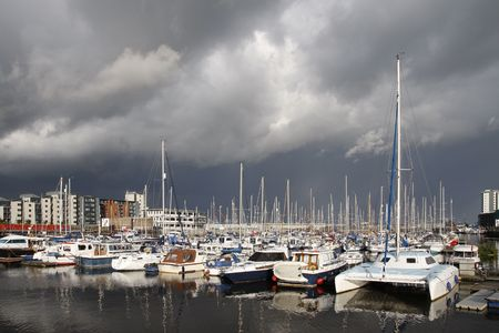 Boats in a marina with dark clouds, stormy sky photo