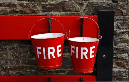 Red fire buckets at an old railway station Stock Photo