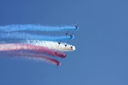 aerobatics: Red Arrows formation flying against a blue sky