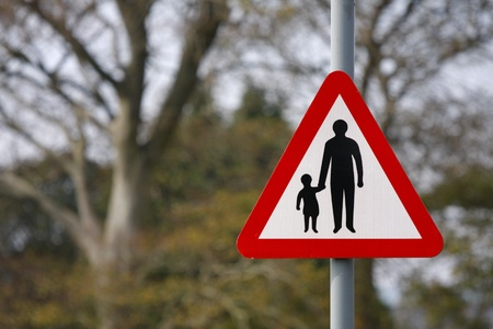Red and white parent and child road safety sign